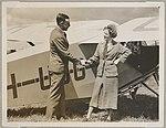 Nancy Bird Walton shaking hands with Elgar Thane (?) of Shell Oil next to de Havilland DH85 Leopard Moth biplane VH-UUG on a field, ca. 1933 (16102203538).jpg