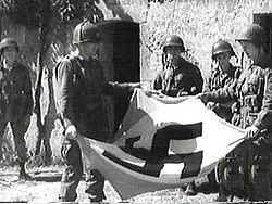 Soldados americanos recolhem uma bandeira nazista, durante a Segunda Guerra Mundial.