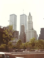 Photograph of the Woolworth Building in 1985 with several sky scrapers, including the towers of the former World Trade Center in the background
