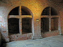 Two brick-built arched wine bins, each divided into four sections, the lower ones being larger than the upper