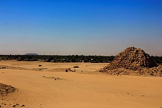 Nuri - The ruins of the pyramid of Taharqa; in the background (left) Gebel Barkal