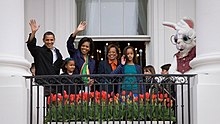 Barack and Michelle Obama, their children, and  her mother, along with a costumed Easter Bunny, on a balcony waving.