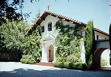 Color photograph of the front of a church showing tall plants flanking an arched entrance, and a gabled roof covered by mission-style curved tiles.
