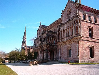 Palacio de Sobrellano en Comillas. Al fondo se puede observar la capilla-panteón construida a modo de pequeña catedral.