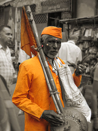 Varkari - A Varkari, carrying an ektari with a saffron flag attached and Chiplya cymbals tied to strings in his hands, journeying from Alandi to Pandharpur