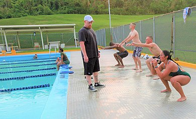Swimmers perform squats as warm-up exercise prior to entering the pool in a U.S. military base, 2011 Participants with the Water Warrior class perform squats prior to entering the pool at Camp Foster, Okinawa, Japan, July 6, 2011 110706-M-VD776-004 (cropped).jpg