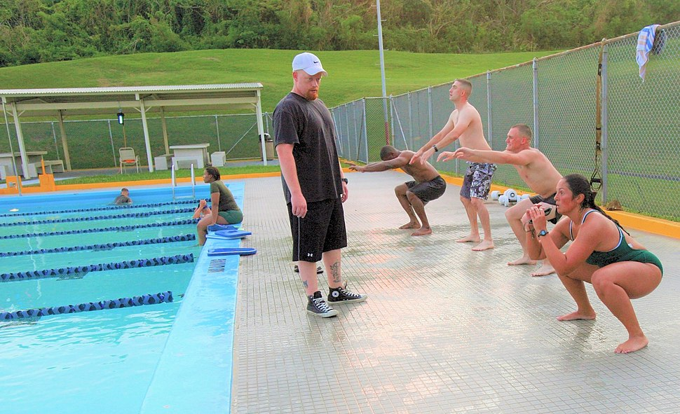 Participants with the Water Warrior class perform squats prior to entering the pool at Camp Foster, Okinawa, Japan, July 6, 2011 110706-M-VD776-004 (cropped)