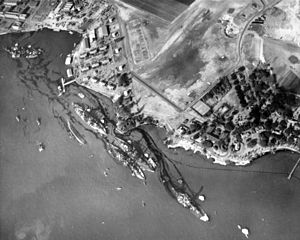 USS Maryland (BB-46) - Aftermath of the Pearl Harbor attack, with Maryland near the top of the photo, shown along with several other sunken battleships