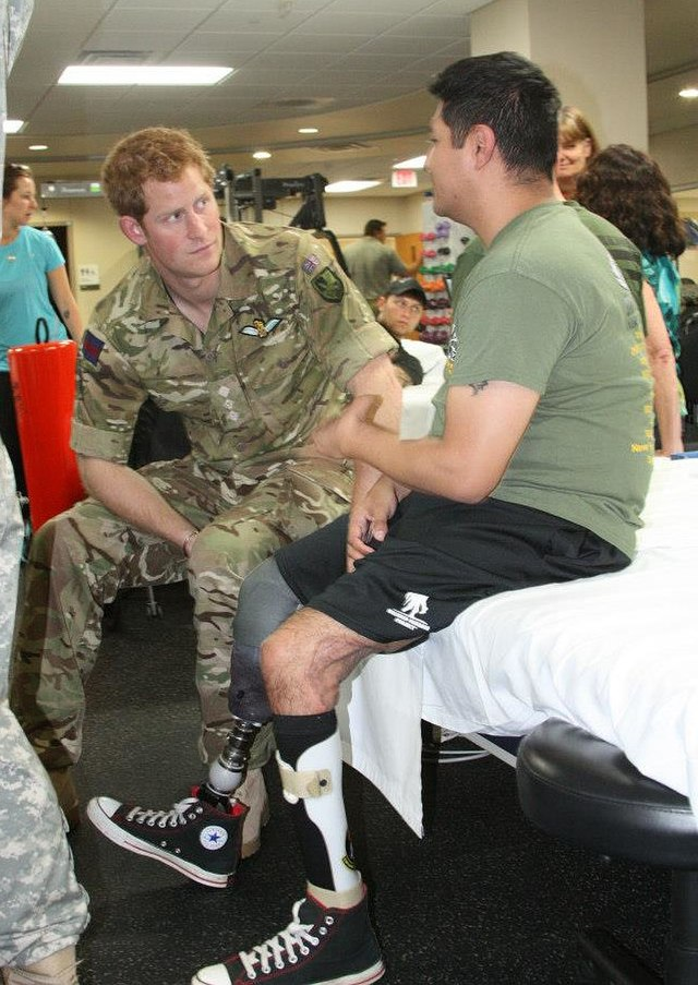 Prince Harry talks to an injured soldier