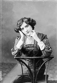 """Retrat de mig cos de l'actriu Pura """"Purita"""" Montoro Rodríguez asseguda, recolzant els braços en el respatller de la cadira."""