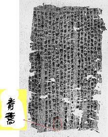 Photographie montrant une page d'un manuscrit écrit en caractères chinois. La page est très abîmée et est parsemée de trous de diverses tailles en bordure et au centre.