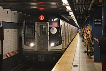 An E train, here composed of R160A cars is seen entering the World Trade Center station. The front of the train contains two white lights providing slight illumination, a window on the right side, the American flag on the left side, and the MTA logo below the flag.