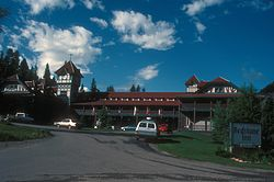"An ornate two-story building with a central clock tower and red roof in the rear of the left side of the image. On the right is a large sign in the foregrounds with ""Redstone Inn"" in large gothic letters, ""Historic Landmark"" in smaller type above it, and ""Restaurant & Bar"" below"