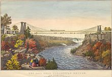 A man and a woman stand in the foreground, viewing a bridge that spans a river.  The bridge is suspended on lines that are supported by two stone towers on each side of the river.  The bridge has two levels; a train travels on the top level, while people and horse-drawn carriages cross on the bottom.  In the far distance is a waterfall.