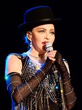 Madonna in a bejeweled dress, black gloves on her hand and a top hat, singing onstage.
