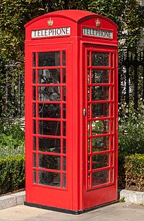 Red telephone box kiosk for a public telephone designed by Sir Giles Gilbert Scott