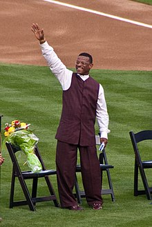 A man in brown pants, a brown vest, and white shirt raises his right hand. He is standing on grass in front of three chairs, one with a bouquet of flowers on it.