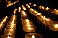 Rows of lit votive candles at night 2009.jpg