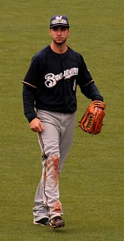 "A man wearing a navy blue jersey with ""Brewers"" on the front in white, gray pants, navy blue cap with a white ""M"", and outfielder's glove on his left hand walking on a grassy field"