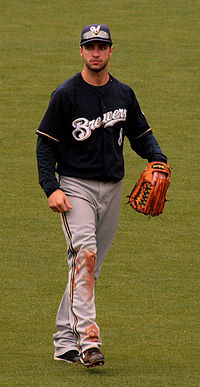 "Portrait of a man in a dark blue baseball jersey with ""BREWERS"" across the chest, grey pants with dirt on the right knee, a baseball glove on his left hand, and a blue cap with an ""M"" on it."