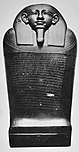 Black and white image of a dark stone coffin with a human face, the coffin stands upright facing the viewer.