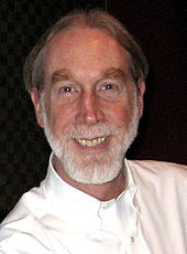 A man grins widely. He wears a white dress shirt and has a full grey beard.