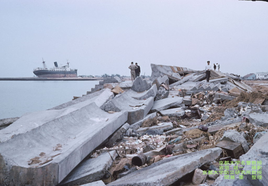 Slightly elevated photo showing a pile of debris near the coast, with some onlookers nearby.