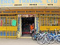 Shop in downtown Honiara selling anything and everything. Shop assistant sitting in the doorway. (10720996516).jpg