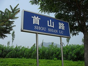 Xingcheng - A Shou Shan Road (首山路) sign featuring the façade of Shoushan (首山) beyond the overgrowth in the background in Xingcheng.