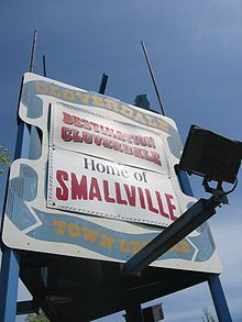 A white billboard with blue ribbon painted around the edges. In the ribbon, the words «Cloverdale Town Centre» appear in yellow surrounding two bannders. The top banner reads, «Destination Cloverdale», while the bottom reads «Home of Smallville».