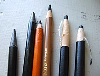 """Two """"woodless"""" graphite pencils in plastic sheaths, two charcoal pencils in wooden sheaths and two charcoal pencils in a paper sheath that is unwrapped as the pencil is used."""