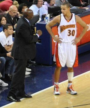 Stephen Curry taking instructions from assista...