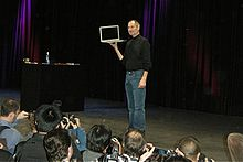 Man in black shirt and jeans holding tablet computer on stage