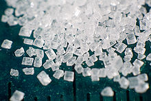 Photograph showing crystals of refined sucrose. A millimetre ruler down the picture shows the scale of the grains is between 0.5 and 1 millimetre.