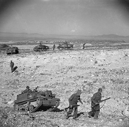 Infantry and carriers of the Grenadier Guards advance over difficult terrain near the Kasserine Pass, 24 February 1943. The British Army in Tunisia 1943 NA880.jpg