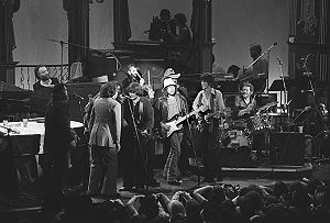 I Shall Be Released - Photograph of The Last Waltz. The Band with Bob Dylan and other guests performing I Shall Be Released. seated behind instruments: Garth Hudson (organ), Ringo Starr (drums), Levon Helm (drums) standing: Dr. John, Neil Diamond, Joni Mitchell (hidden), Neil Young, Rick Danko (Bass), Van Morrison, Bob Dylan (guitar), Ronnie Hawkins, Robbie Robertson (guitar) not shown: Richard Manuel, Eric Clapton, Ron Wood
