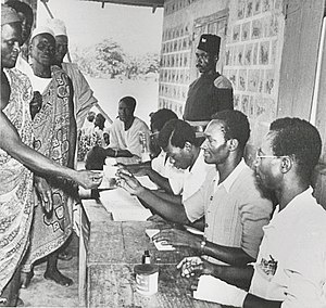Gold Coast legislative election, 1956 - A voter receives a ballot paper from a polling assistant at Kumbungu Polling Station in the Northern Territories.