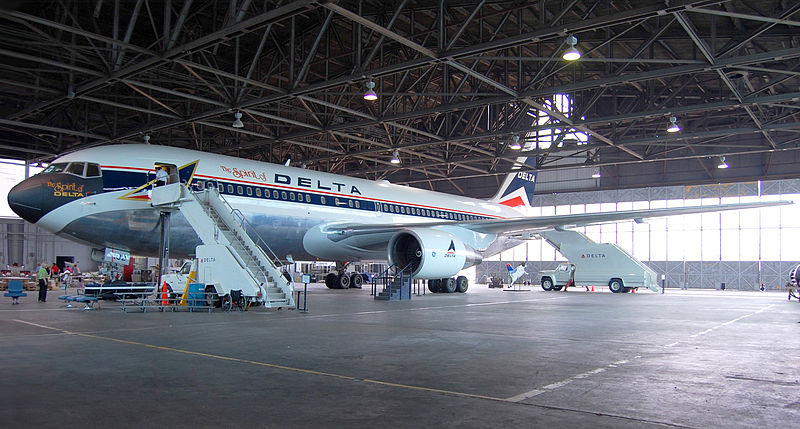 Side view of a parked Delta Air Lines twin-engine jet in hangar, with stairs mounted next to the aircraft's forward door.