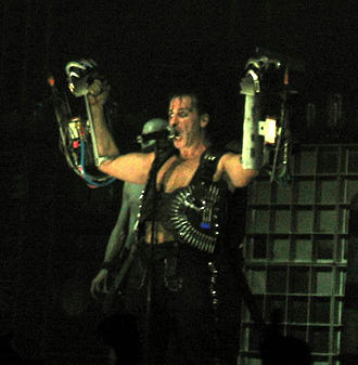"Till Lindemann performing ""Rammstein"", during which he wears dual arm-mounted flamethrowers Till-Lindemann.jpg"