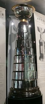 A large silver trophy made of individual bands that become progressively smaller as they approach the top, where a bowl is affixed.