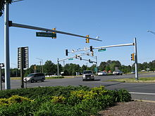 Several cars pass through a signalized intersection viewed from behind planted shrubs. Small green signs on the traffic light pole masts indicate the roads are named Ocean Highway and Worcester Highway.