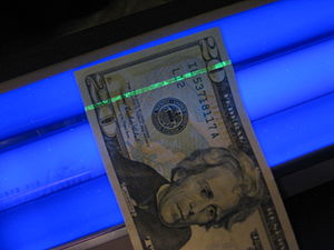 The security strip in a twenty-dollar bill glows green under a blacklight. US $20 under blacklight.jpg