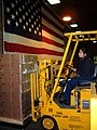 US Navy 030407-N-5821W-001 Storekeeper Seaman Estella Perez operates a forklift in order to weigh a pallet of Tastykake snacks.jpg