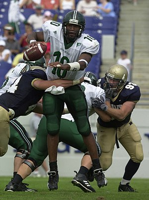 2003 Eastern Michigan Eagles football team - EMU junior quarterback Chinedu Okoro being tackled by Navy junior linebacker Lane Jackson.