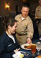 US Navy 040420-N-6278K-058 Lt. Cmdr. Daniel Pollard, the Deck Department 1st Lt. aboard USS George Washington (CVN 73), of Lewiston, N.Y., serves Culinary Specialist Seaman Paulina Ransom, of Tricity, Wash., dinner.jpg