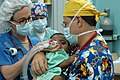 US Navy 060702-N-3532C-010 Operation Smile volunteers Janet Casabon Benowitz and Dr. Bill Pond anesthetize a young child before undergoing corrective plastic surgery on his cleft lip.jpg