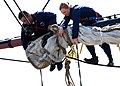 US Navy 070530-N-2893B-001 About 100 feet above the deck of USS Constitution, Yeoman 1st Class Rob Santiago and Seaman Nola Sparks bend a 500-lb., 158-square yard cotton canvas sail.jpg