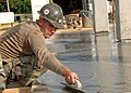 US Navy 081216-N-8816D-025 Builder Constructionman Joseph Coyle uses a float to smooth wet concrete.jpg