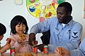 US Navy 090301-N-2610F-007 Boatswain's Mate 3rd Class Barn Henderson, from Chicago, opens a can of apple juice for a child in the Kodomono-Ie Children's Home during a community service project.jpg