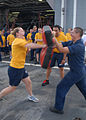 US Navy 110708-N-DU438-604 Ensign Lindayle Fredrick punches a bag after being sprayed with oleoresin capsicum spray during security training aboard.jpg